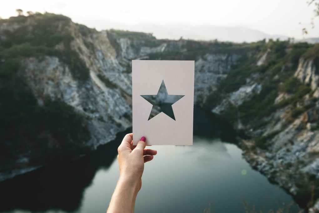 person holding star cutout paper facing mountain