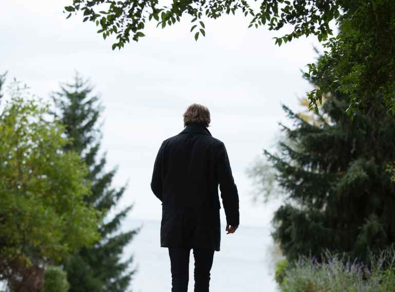 shallow focus photography of man wearing black coat and black pants standing beside green trees